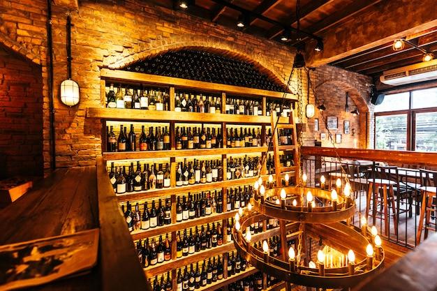 イタリアンレストランの壁のワインセラーは、居心地の良い雰囲気を演出する暖かい光の中でレンガで装飾されています。