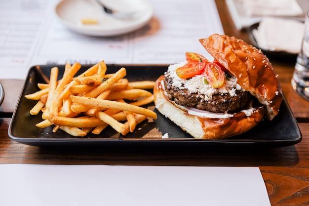 Чизбургер с жареной говядиной, сыром фета и нарезанными помидорами, подается с картофелем фри в черной тарелке.
