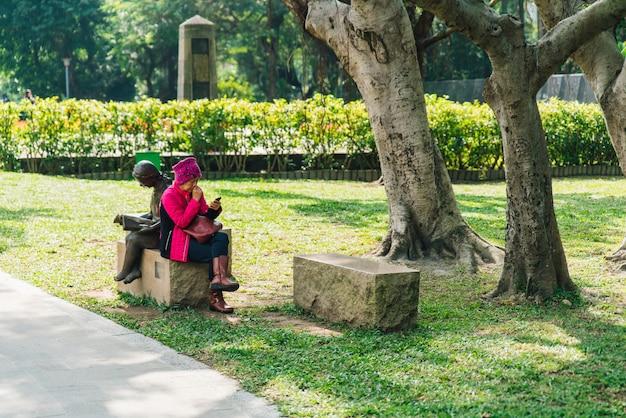 観光客の女性が座っていると公園の立方体の石の座席に彼女の電話を見ています。