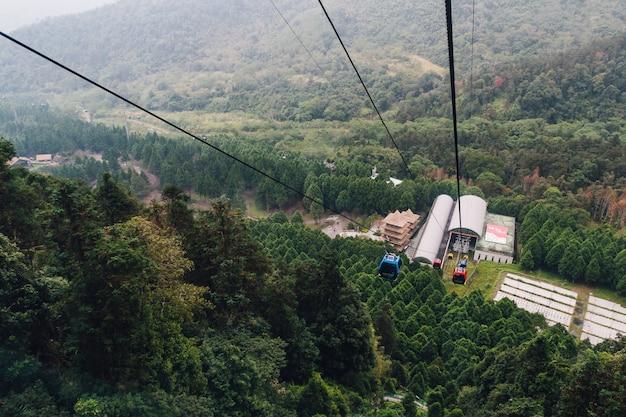 Гондольный подъемник движется от станции над горой с зелеными деревьями