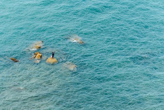タイのチョンブリで釣りのための海の波の中で石の上に立っている漁師の空撮。
