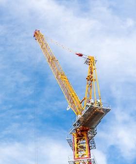 クレーンがタイのバンコクでバックグラウンドで雲と青空と工事現場で働いています。