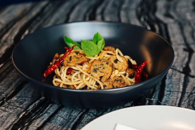 Рецепт сушеных спагетти с чили и северной тайской колбасой (сай уа) подается в черной тарелке с белой тарелкой и столовыми приборами.