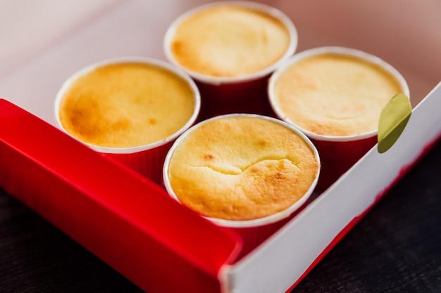 紙箱にクローズアップチーズカップ。なめらかで豊かな乳白色の味。