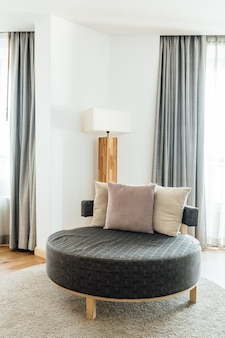 Круглый диван с подушками в главной спальне оформлен в светлых и теплых тонах.