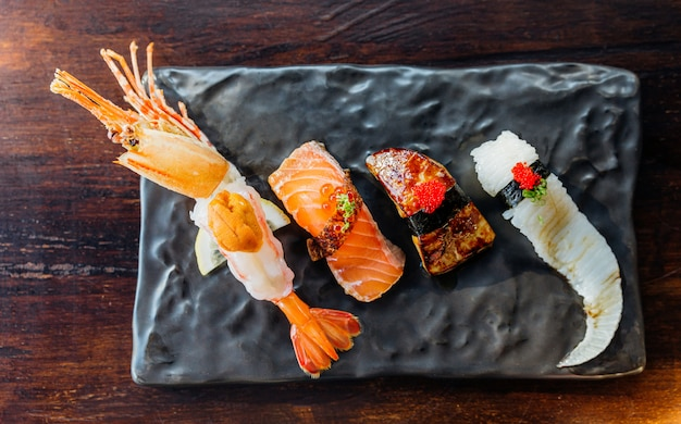 プレミアム寿司セットのトップビューには、ウニ、フォアグラ、サーモン、えんがわを添えたエビフライが含まれます。