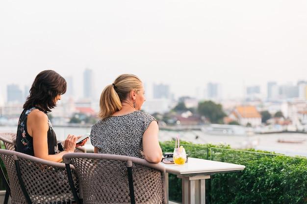 Европейские женщины сидят и смотрят на ват арун (храм рассвета) у реки чаопрайя.