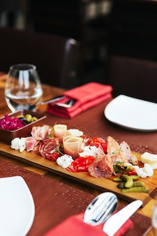生ハム、ベーコン、サラミ、ソーセージと木の板のコールドカット。肉の盛り合わせ前菜には、カトラリー付きのダイニングテーブルにピクルスとオリーブが添えられています。