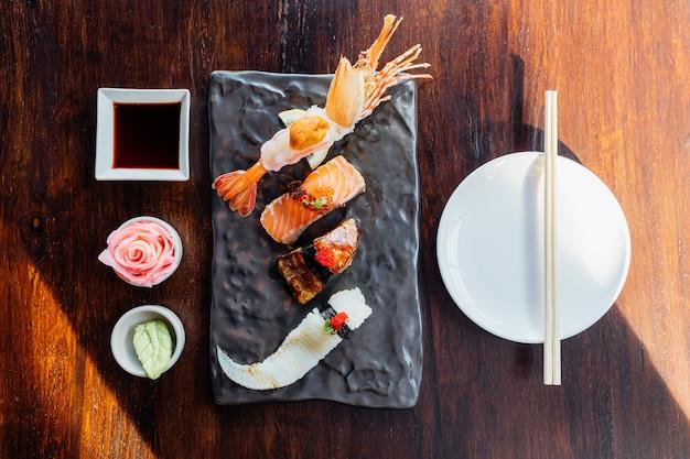 プレミアム寿司セットのトップビューには、ウニ、フォアグラ、サーモン、えんがわを添えた揚げエビが含まれます。