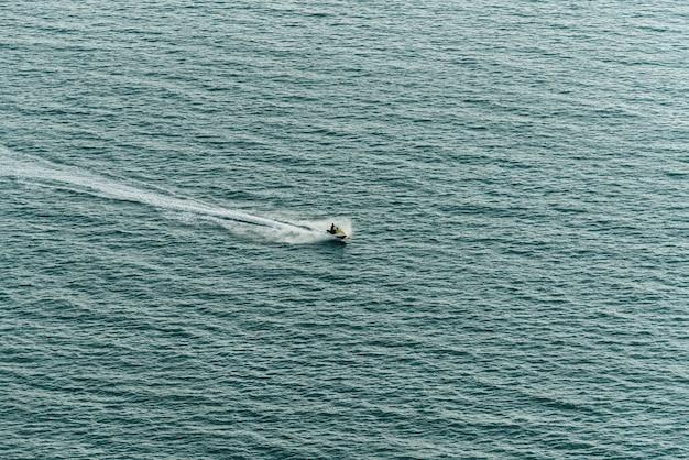 Укомплектуйте личным составом освобождающ водный мотоцикл на море с брызгая след воды на поверхности моря около пляжа паттайя.
