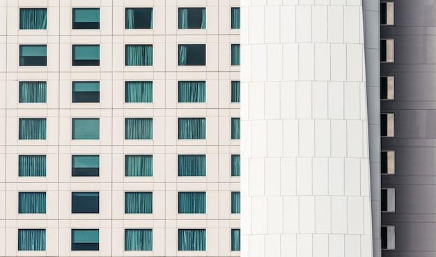 Современный фасад здания с оконным стеклом и белой железной оболочкой здания.