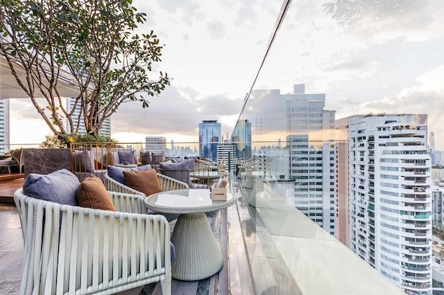 Открытый бар на крыше с наружными диванами в вечернее время. из этого пространства открывается вид на современные здания в бангкоке.