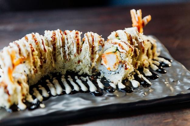 クローズアップの巻き寿司とご飯、エビの天ぷら、アボカド、チーズをカバーしたシャキッとした天ぷら粉照り焼きソースとマヨネーズのトッピング。