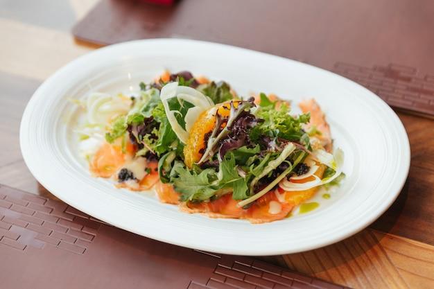 スモークサーモンポメロサラダには、グリーンオーク、レッドリーフレタス、タマネギが含まれます