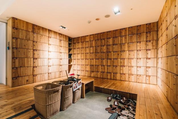 Деревянный шкафчик для обуви внутри стойки регистрации хостела. современный, сдержанный и чистый дизайн в тайбэе, тайвань.