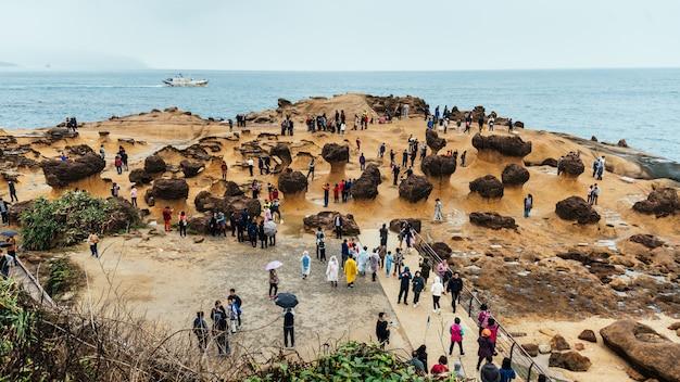 台湾の北海岸の岬である野柳地質公園を歩く観光客の多様性。海に浸食されたハチの巣とキノコの岩の風景。