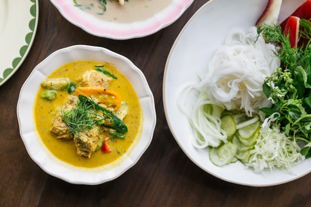 カニ肉のカレーソース添えライスヌードルのトップビュー、野菜添え。クラシックなタイ料理。