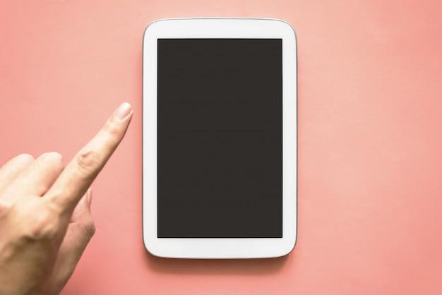 黒い画面とピンクの紙の色の背景に触れる手で白い色のタブレットの平面図です。