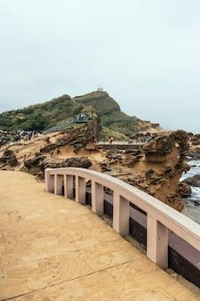 Разнообразие туристов, гуляющих в геопарк йелиу, мыс на северном побережье тайваня. пейзаж соты и грибных скал, разрушенных морем. закройте на каменный мост.