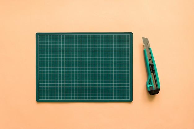 淡いオレンジ色の紙の背景に緑色のカッターで緑色のゴム製カッティングマットの平面図。コピースペースの背景。