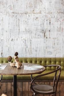緑のソファ、木製のテーブル、黒いスチールの椅子、白いスクラッチテクスチャの壁紙で飾られたダイニングエリア。モダンなインテリアのレストランの雰囲気。