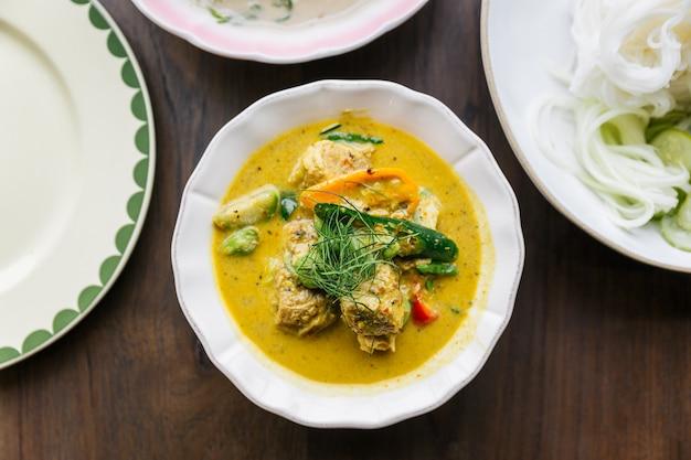 Вид сверху рисовой лапши с крабовым мясом и соусом карри, подается с овощами. классическая тайская кухня.