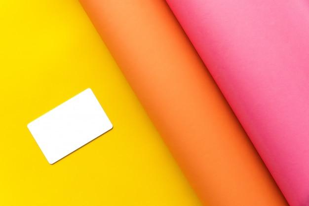 抽象的な形で黄色の色紙の上に一緒に曲げてピンクとオレンジの紙で白い空白の名刺。コピースペースで抽象的な紙の背景。