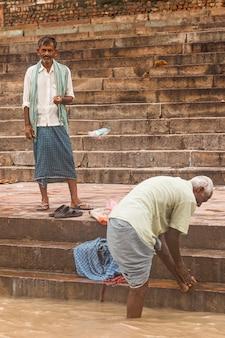 インド、ウッタルプラデーシュ州、バラナシのガンジス川(ガンジス川)沿いの背景にある古い建物とガートに住んでいるインド人のストリート写真。