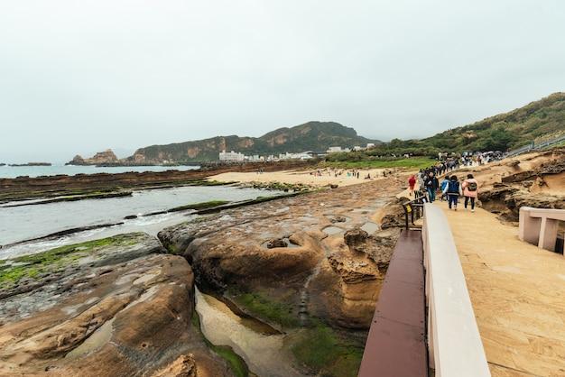 Ландшафт геопарка йелиу, мыса на северном побережье тайваня. пейзаж сот и грибных скал, разрушенных морем, на фоне городских зданий.
