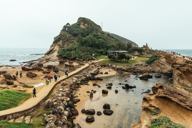 台湾の北海岸の岬である野柳地質公園を歩く観光客の空撮の多様性。海に浸食されたハニカムとキノコの岩の風景。