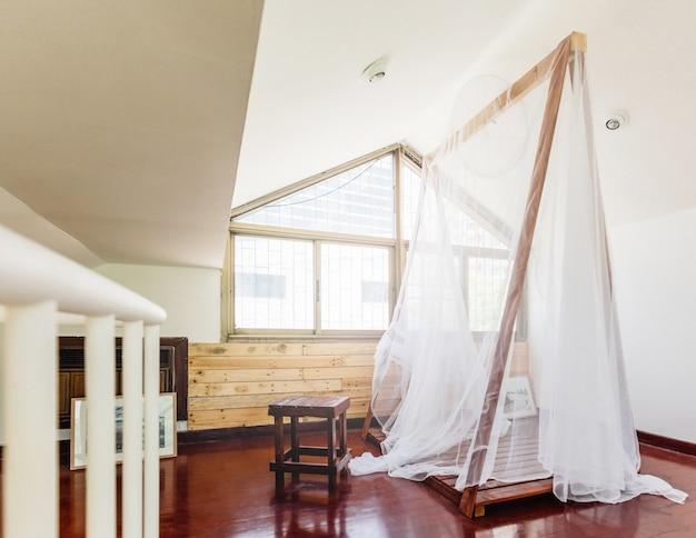 窓からの自然光が入る家の中の木製構造のテントの薄い白い布。
