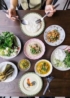 カニ肉カレーソース添えライスヌードルの平面図、野菜添え。スパイシーな豚ひき肉のハーブ炒め。ピリ辛サクサクの豚皮とキノコのスープ。スチームライスと古典的なタイ料理。