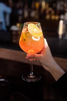 Апельсиновый фруктовый коктейль, который смешивают с ломтиками апельсина и личи в бокале. рука достает бокал для коктейля до естественного света.
