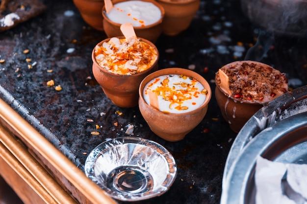 Популярный индийский напиток ласси (традиционный напиток на основе йогурта дахи) в глиняной чашке с различными начинками на улице в варанаси.