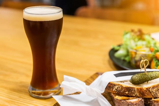 Стаут (черное пиво) с пенкой в стакане на деревянном столе с размытыми продуктами