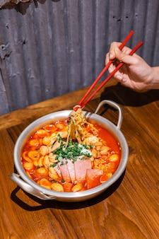 Рука сжимая лапшу палочками. традиционный корейский рамэн суп с кимчи, ветчиной, колбасой и сыром в серебряная чаша на деревянный стол. корейская кухня вкусная азиатская еда.