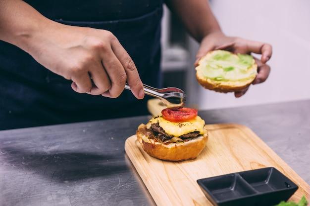 Шеф-повар добавить нарезанный помидор для приготовления говяжьего чизбургер на деревянной тарелке