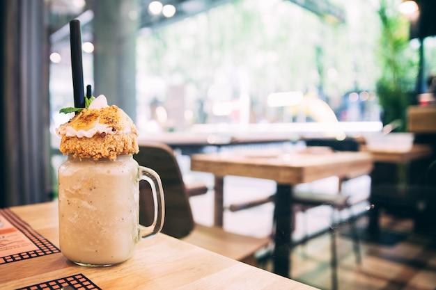 Банановый молочный коктейль с яблоком рубит и нарезанный бананами на деревянном столе