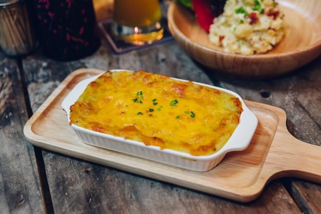 Горячая испеченная лазань с сырной плавящей поверхностью подается в деревянной тарелке.