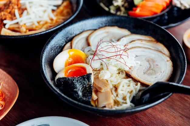 味噌スープ、チャーシューポーク、ゆで卵、干し海草の日本ヌードル。