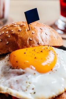 揚げた卵と旗を持つおいしいハンバーガーは、木製のテーブルの黒いプレートにフライドポテトを添えました。