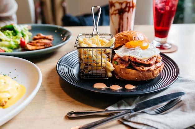 揚げた卵とおいしいハンバーガーは、木製のテーブルの黒いプレートにフライドイ添え。