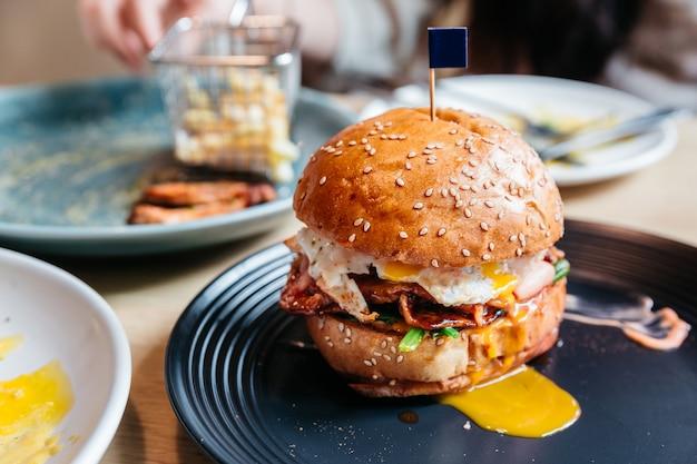 揚げた卵と卵黄を持つおいしいハンバーガーは、木製のテーブルの黒いプレートにフライドポテトを添えました。