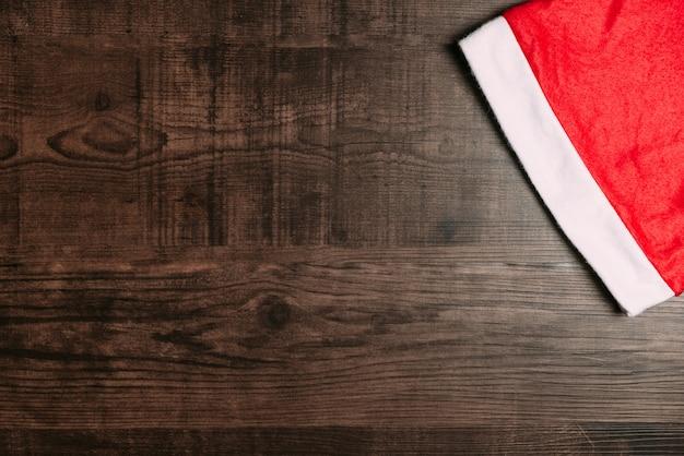 木製の背景にサンタの帽子。クリスマスと新年の幸せのためのフラットなレイアウト。