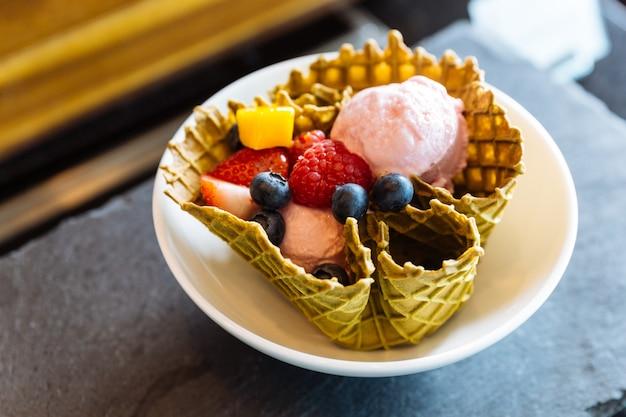 クリスピーな薄いワッフルボウルの内側に新鮮な果物を入れたイチゴのアイスクリーム。