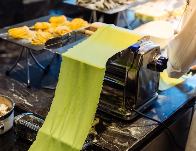 手作りの新鮮なホウレンソウのフェツチンパスタを作るための生地を回転させるシェフ。