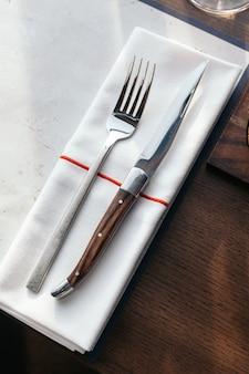 木製テーブルにナプキンをかけたナイフとフォーク。ラグジュアリーカトラリーセット。