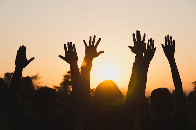 空の背景に強いパワーを披露して腕を上げる人々の手。