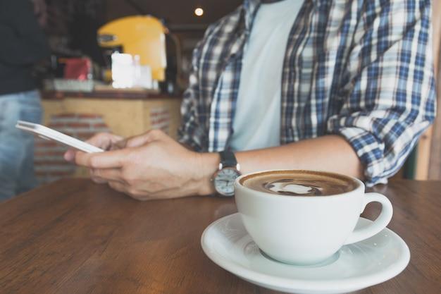 木製のテーブルにコーヒーカップとスマートフォンを使用して男性。