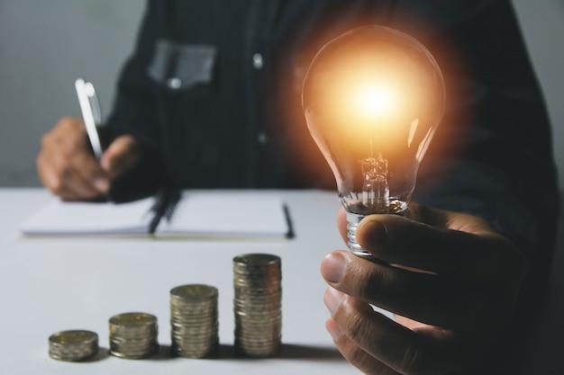 会計と創造的な概念のためのコインのスタックと電球を保持する男性の手。